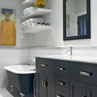 Cette image montre une douche en alcôve principale traditionnelle de taille moyenne avec une baignoire sur pieds, carrelage en mosaïque, un placard en trompe-l'oeil, des portes de placards vertess, un carrelage blanc, un mur gris, un sol en marbre, un lavabo encastré et un plan de toilette en marbre.