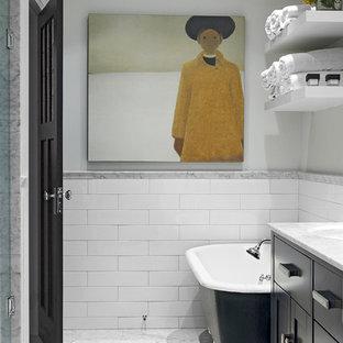 Modelo de cuarto de baño principal, clásico, de tamaño medio, con bañera con patas, baldosas y/o azulejos de cemento, suelo de mármol, armarios tipo mueble, puertas de armario verdes, ducha empotrada, baldosas y/o azulejos blancos, lavabo bajoencimera, encimera de mármol y paredes grises