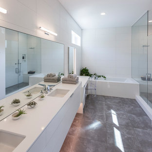 Minimalist white tile gray floor alcove bathtub photo in Cincinnati with flat-panel cabinets, white cabinets, white walls, a hinged shower door, white countertops and an undermount sink