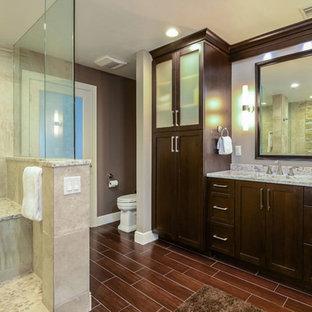Foto de cuarto de baño principal, clásico renovado, de tamaño medio, con armarios estilo shaker, puertas de armario de madera en tonos medios, ducha esquinera, sanitario de dos piezas, baldosas y/o azulejos beige, baldosas y/o azulejos de cerámica, paredes grises, suelo vinílico, lavabo bajoencimera, encimera de granito, suelo marrón y ducha abierta