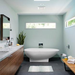 Ejemplo de cuarto de baño principal, vintage, grande, con armarios con paneles lisos, puertas de armario de madera en tonos medios, encimera de mármol, bañera exenta, paredes azules, suelo de pizarra, lavabo bajoencimera, baldosas y/o azulejos grises y suelo gris