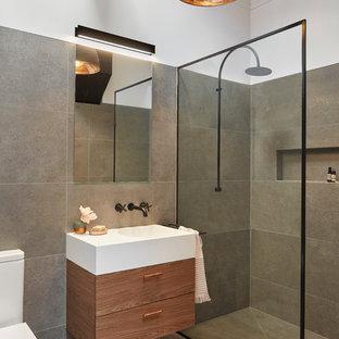 На фото: маленькая ванная комната в стиле лофт с плоскими фасадами, темными деревянными фасадами, открытым душем, унитазом-моноблоком, серой плиткой, керамогранитной плиткой, полом из керамогранита, душевой кабиной, монолитной раковиной, столешницей из искусственного камня, серым полом и открытым душем с