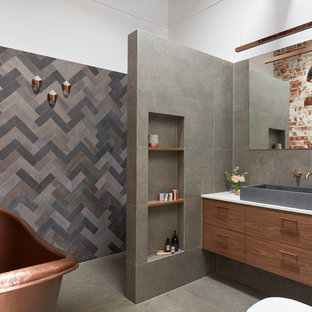 Inspiration for a large industrial master bathroom in Melbourne with flat-panel cabinets, a freestanding tub, an alcove shower, a one-piece toilet, gray tile, porcelain tile, white walls, porcelain floors, a vessel sink, engineered quartz benchtops, grey floor, an open shower, medium wood cabinets and white benchtops.