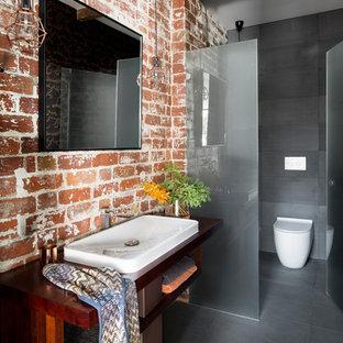 Modelo de cuarto de baño con ducha, urbano, con armarios abiertos, puertas de armario de madera en tonos medios, sanitario de una pieza, baldosas y/o azulejos rojos, paredes multicolor, suelo de baldosas de porcelana, lavabo encastrado, encimera de madera, suelo gris y encimeras marrones