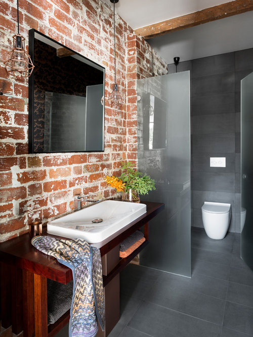 industrial home design. industrial 3/4 bathroom in melbourne with open cabinets, dark wood a home design