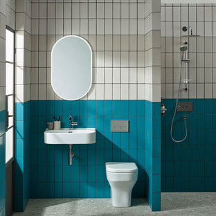 Photo of a contemporary bathroom in Other with a one-piece toilet, beige tiles, blue tiles, white tiles, metro tiles, multi-coloured walls, a wall-mounted sink, grey floors and an open shower.