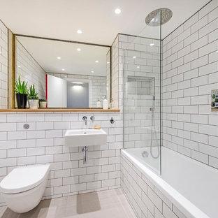 Industriell inredning av ett mellanstort badrum, med ett väggmonterat handfat, ett badkar i en alkov, en dusch/badkar-kombination, en vägghängd toalettstol, vit kakel och tunnelbanekakel