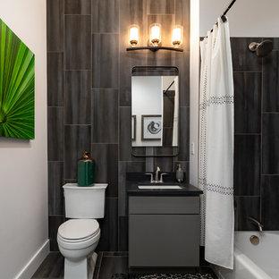 Ispirazione per una stanza da bagno design con ante lisce, ante grigie, vasca ad alcova, vasca/doccia, WC a due pezzi, piastrelle nere, pareti nere, lavabo sottopiano, pavimento nero, doccia con tenda e top nero