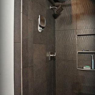 ポートランドの中サイズのインダストリアルスタイルのおしゃれなマスターバスルーム (一体型シンク、ドロップイン型浴槽、オープン型シャワー、一体型トイレ、グレーのタイル、磁器タイル、グレーの壁、コンクリートの床、フラットパネル扉のキャビネット、黒いキャビネット、ステンレスの洗面台) の写真