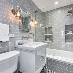 Foto di una piccola stanza da bagno padronale industriale con ante bianche, vasca da incasso, WC a due pezzi, piastrelle grigie, piastrelle in ceramica, pareti grigie, pavimento con piastrelle in ceramica, lavabo sottopiano e top in marmo