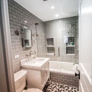 Ispirazione per una piccola stanza da bagno padronale industriale con ante bianche, vasca da incasso, WC a due pezzi, piastrelle grigie, piastrelle in ceramica, pareti grigie, pavimento con piastrelle in ceramica, lavabo sottopiano e top in marmo