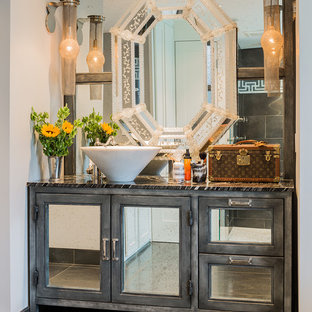 This is an example of an industrial bathroom in Boston with a vessel sink, glass-front cabinets, grey cabinets and gray tile.