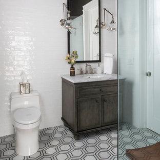 Immagine di una stanza da bagno con doccia industriale di medie dimensioni con consolle stile comò, ante grigie, WC monopezzo, pareti grigie, pavimento in marmo, lavabo sottopiano, top in marmo, piastrelle bianche e piastrelle in gres porcellanato