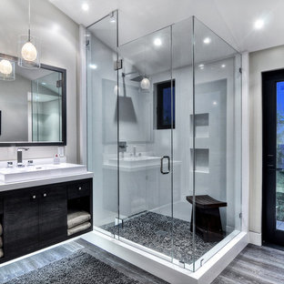 Bathroom - mid-sized contemporary master gray tile and stone tile concrete floor and gray floor bathroom idea in Orange County with a vessel sink, flat-panel cabinets, black cabinets, a one-piece toilet, white walls, granite countertops and a hinged shower door