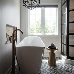 На фото: главная ванная комната среднего размера в стиле лофт с фасадами в стиле шейкер, фасадами цвета дерева среднего тона, отдельно стоящей ванной, угловым душем, раздельным унитазом, желтой плиткой, плиткой кабанчик, серыми стенами, полом из цементной плитки, врезной раковиной, столешницей из искусственного кварца, серым полом, душем с распашными дверями и белой столешницей с