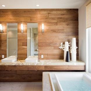 Пример оригинального дизайна: большая главная ванная комната в современном стиле с настольной раковиной, столешницей из оникса, белой плиткой, керамической плиткой, полом из керамической плитки, накладной ванной, коричневыми стенами и бежевой столешницей