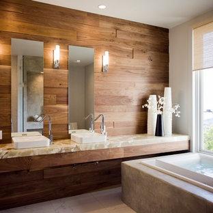 Imagen de cuarto de baño principal, actual, grande, con lavabo sobreencimera, puertas de armario de madera oscura, encimera de ónix, bañera exenta, baldosas y/o azulejos blancos, baldosas y/o azulejos de porcelana, paredes blancas y suelo de baldosas de cerámica