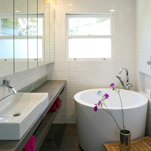 Immagine di una piccola stanza da bagno moderna con ante lisce, vasca giapponese, vasca/doccia, bidè, piastrelle bianche, piastrelle in gres porcellanato, pareti bianche, pavimento in pietra calcarea, lavabo a bacinella e top in pietra calcarea