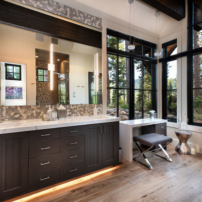 Large mountain style master multicolored tile and pebble tile medium tone wood floor and brown floor bathroom photo in Other with recessed-panel cabinets, dark wood cabinets, white walls, an undermount sink, white countertops and marble countertops
