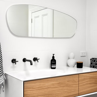 Inspiration for a mid-sized contemporary bathroom in Sydney with flat-panel cabinets, medium wood cabinets, white tile, white walls, an integrated sink, white benchtops, porcelain tile, porcelain floors, solid surface benchtops and grey floor.