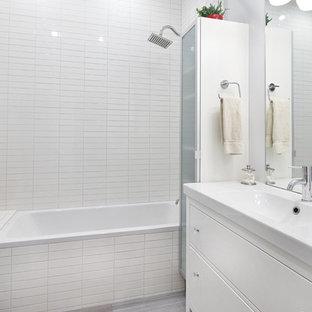 Exempel på ett litet modernt en-suite badrum, med ett integrerad handfat, luckor med infälld panel, vita skåp, ett platsbyggt badkar, en dusch/badkar-kombination, en toalettstol med hel cisternkåpa, grå kakel, keramikplattor, grå väggar och klinkergolv i porslin