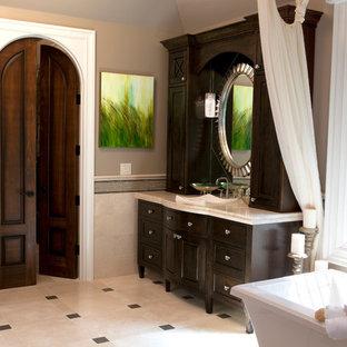 Ejemplo de cuarto de baño principal, clásico, con lavabo sobreencimera, puertas de armario de madera en tonos medios, bañera exenta, baldosas y/o azulejos beige, armarios con paneles empotrados, paredes grises y suelo de baldosas de cerámica