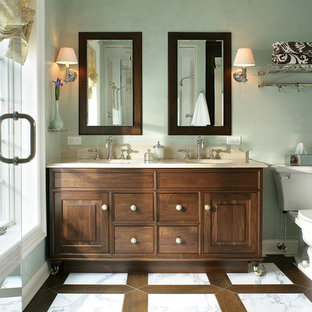 Inspiration for a mid-sized traditional master bathroom in New York with dark wood cabinets, a two-piece toilet, white tile, stone tile, green walls, marble floors, an undermount sink, limestone benchtops, raised-panel cabinets, an alcove shower, white floor and a hinged shower door.