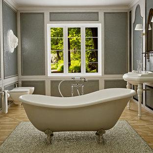 Immagine di una stanza da bagno american style di medie dimensioni con vasca freestanding, WC sospeso, piastrelle beige, piastrelle effetto legno, pareti grigie e pavimento in legno massello medio