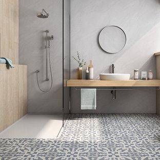 На фото: ванная комната среднего размера в современном стиле с открытыми фасадами, серыми фасадами, душевой комнатой, серой плиткой, цементной плиткой, серыми стенами, полом из керамогранита, душевой кабиной, настольной раковиной, столешницей из дерева, разноцветным полом и открытым душем с