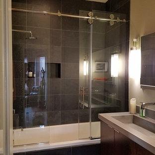 Mittelgroßes Modernes Duschbad mit flächenbündigen Schrankfronten, dunklen Holzschränken, Badewanne in Nische, Duschbadewanne, Toilette mit Aufsatzspülkasten, schwarzen Fliesen, Schieferfliesen, beiger Wandfarbe, Schieferboden, integriertem Waschbecken, Beton-Waschbecken/Waschtisch, schwarzem Boden und Schiebetür-Duschabtrennung in Baltimore
