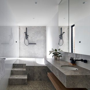 Mid-sized contemporary bathroom in Melbourne with flat-panel cabinets, an undermount tub, white tile, ceramic tile, white walls, limestone floors, an undermount sink, limestone benchtops, grey floor, an open shower, grey benchtops and a curbless shower.
