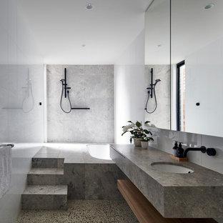 Réalisation d'une salle de bain design de taille moyenne avec un placard à porte plane, une baignoire encastrée, un carrelage blanc, des carreaux de céramique, un mur blanc, un sol en calcaire, un lavabo encastré, un plan de toilette en calcaire, un sol gris, aucune cabine, un plan de toilette gris et une douche à l'italienne.