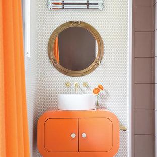 Modern inredning av ett litet orange oranget badrum med dusch, med släta luckor, orange skåp, vit kakel, vita väggar, ett fristående handfat, bänkskiva i akrylsten och vitt golv