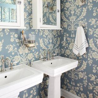 Shabby chic-inspirerad inredning av ett mellanstort en-suite badrum, med ett piedestal handfat, blå väggar, mörkt trägolv, luckor med glaspanel och vita skåp