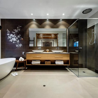 Modelo de cuarto de baño principal, asiático, grande, con lavabo sobreencimera, armarios con paneles lisos, puertas de armario de madera oscura, bañera exenta, ducha esquinera, baldosas y/o azulejos marrones y paredes blancas