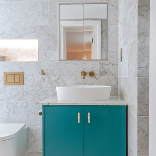 Photo of a large contemporary master bathroom in London with flat-panel cabinets, turquoise cabinets, an open shower, a wall-mount toilet, gray tile, ceramic tile, grey walls, ceramic floors, a vessel sink, marble benchtops, white floor, an open shower, grey benchtops, a single vanity and a freestanding vanity.