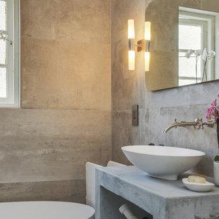 Immagine di una piccola stanza da bagno con doccia contemporanea con vasca freestanding, piastrelle grigie, piastrelle di cemento, pareti grigie, pavimento in cemento e top in cemento