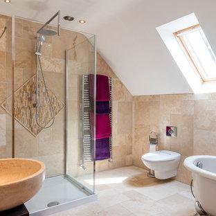 Cette image montre une salle de bain méditerranéenne de taille moyenne avec une baignoire indépendante, une douche d'angle, un WC suspendu, un carrelage beige, un mur beige, une vasque, un sol beige et un plan de toilette noir.