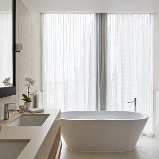 Modernes Badezimmer En Suite mit flächenbündigen Schrankfronten, beigen Schränken, freistehender Badewanne, Wandtoilette, beigefarbenen Fliesen, beiger Wandfarbe, Unterbauwaschbecken, beigem Boden, Falttür-Duschabtrennung und beiger Waschtischplatte in Melbourne
