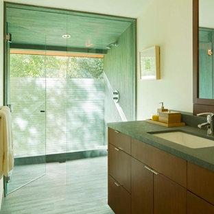 Imagen de cuarto de baño principal, minimalista, grande, con armarios con paneles lisos, puertas de armario de madera en tonos medios, ducha a ras de suelo, sanitario de pared, baldosas y/o azulejos verdes, baldosas y/o azulejos de pizarra, paredes blancas, suelo de pizarra, lavabo bajoencimera, encimera de esteatita, suelo verde y ducha con puerta con bisagras