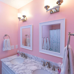 Example of a small transitional kids' white tile porcelain floor tub/shower combo design in Cleveland with shaker cabinets, white cabinets, a two-piece toilet, pink walls, an undermount sink and quartz countertops