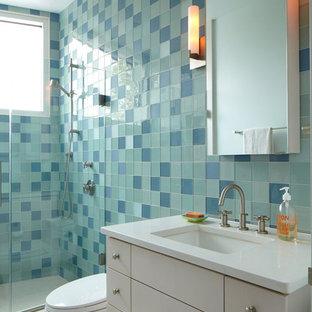 Cette image montre une douche en alcôve minimaliste avec un lavabo encastré, un placard à porte plane, des portes de placard blanches, un carrelage bleu et un carrelage en pâte de verre.