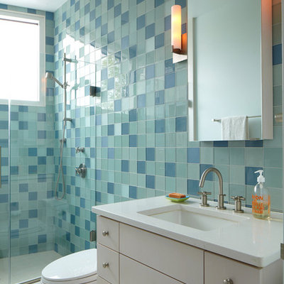 Example of a minimalist blue tile and glass tile alcove shower design in New York with an undermount sink, flat-panel cabinets and white cabinets