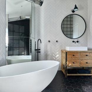 Неиссякаемый источник вдохновения для домашнего уюта: главная ванная комната среднего размера в современном стиле с светлыми деревянными фасадами, отдельно стоящей ванной, белой плиткой, керамической плиткой, белыми стенами, настольной раковиной, столешницей из дерева, черным полом, фасадами островного типа, коричневой столешницей, открытым душем, инсталляцией, полом из керамогранита и открытым душем