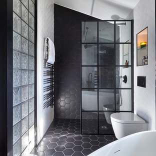 Medium sized contemporary bathroom in London with a wall mounted toilet, white walls, black floors, an open shower, black and white tiles, freestanding cabinets, medium wood cabinets, a freestanding bath, porcelain tiles, porcelain flooring, a vessel sink and wooden worktops.