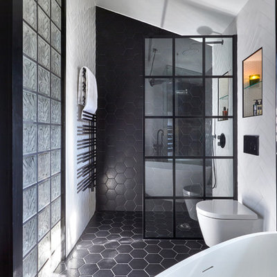 Bathroom - mid-sized contemporary master black and white tile and porcelain tile black floor and porcelain tile bathroom idea in London with a wall-mount toilet, white walls, furniture-like cabinets, medium tone wood cabinets, a vessel sink and wood countertops