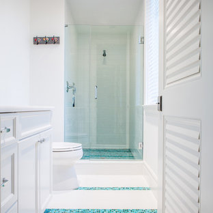 Ejemplo de cuarto de baño infantil, marinero, de tamaño medio, con lavabo bajoencimera, armarios con paneles empotrados, puertas de armario blancas, encimera de cuarzo compacto, ducha empotrada, sanitario de una pieza, baldosas y/o azulejos azules, baldosas y/o azulejos de vidrio laminado, paredes blancas y suelo de baldosas de cerámica