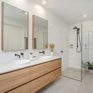 This is an example of a large contemporary 3/4 bathroom in Gold Coast - Tweed with light wood cabinets, an alcove shower, white walls, porcelain floors, a vessel sink, grey floor, an open shower, white benchtops, a double vanity and a floating vanity.