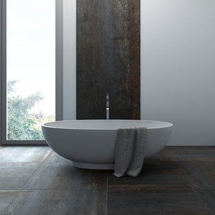 Foto de cuarto de baño principal, moderno, grande, con bañera exenta, paredes grises, suelo de pizarra y suelo negro