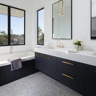 Immagine di una stanza da bagno padronale design con ante lisce, ante nere, vasca sottopiano, pareti bianche, lavabo integrato e pavimento grigio